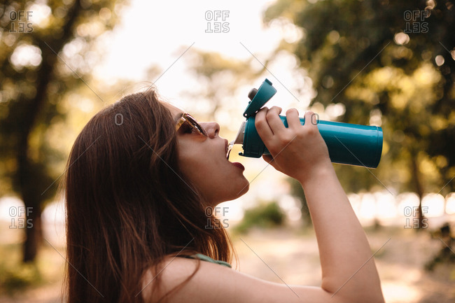 Young woman drinking water from reusable bottle in summer park