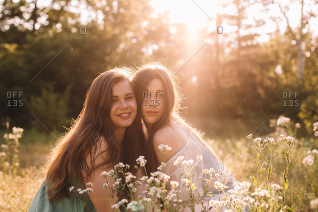 Portrait of happy lesbian couple sitting amidst flowers in summer
