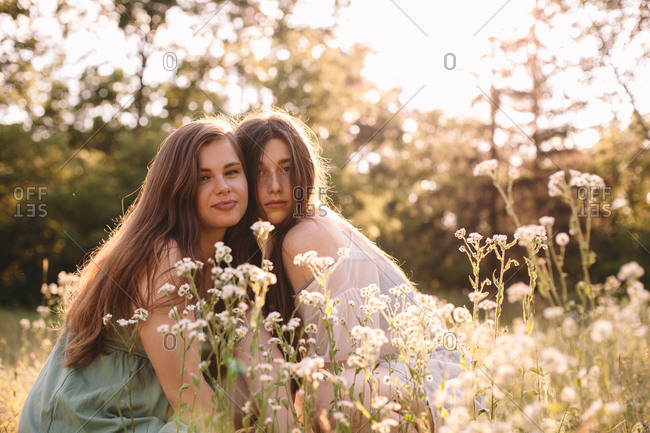 Portrait of lesbian couple sitting amidst flowers in summer forest
