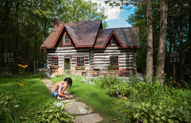 Boy squatting on a path to a log cabin cottage on a summer day.