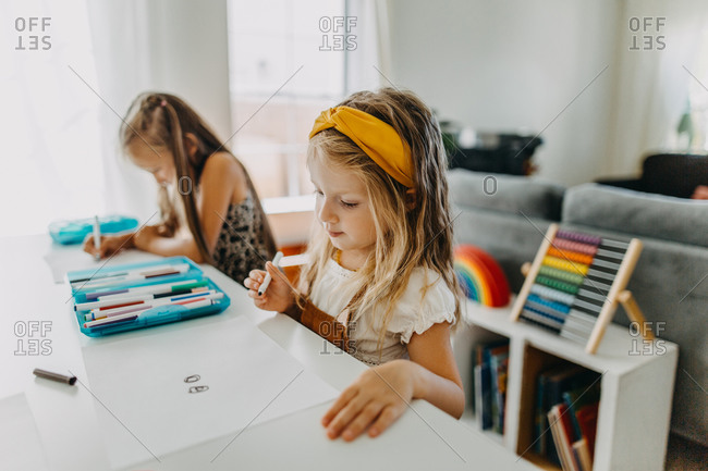 Two girls drawing with colorful markers and paper and smiling at work