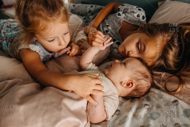 Two girls touching baby sibling and cuddling in bed together