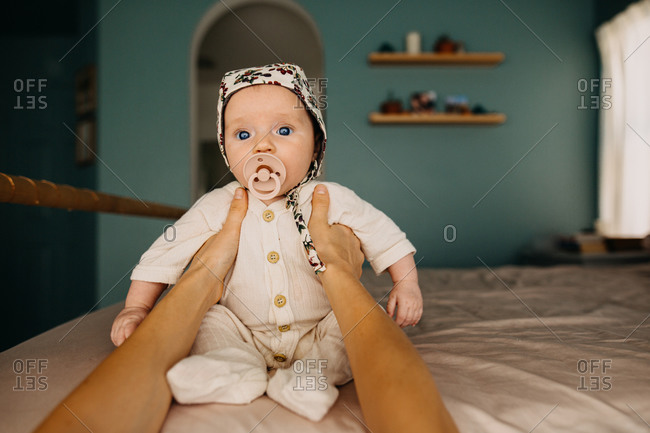 Young infant in a bonnet sitting on bed with help from a mothers hands
