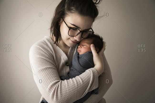 Modern Millennial Hipster Mom Snuggles Swaddled Newborn Baby Son