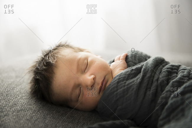 Backlit Sleeping Newborn With Lots of Hair Faces Camera