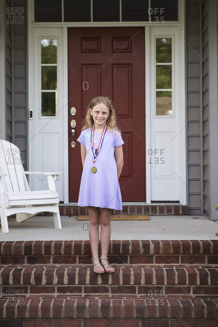 Smiling Blonde Girl Wearing Medal Standing on Brick Front Porch