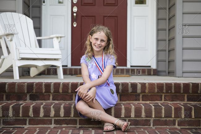 Smiling Blonde Girl Wearing A Medal Sits on Front Brick Front Steps