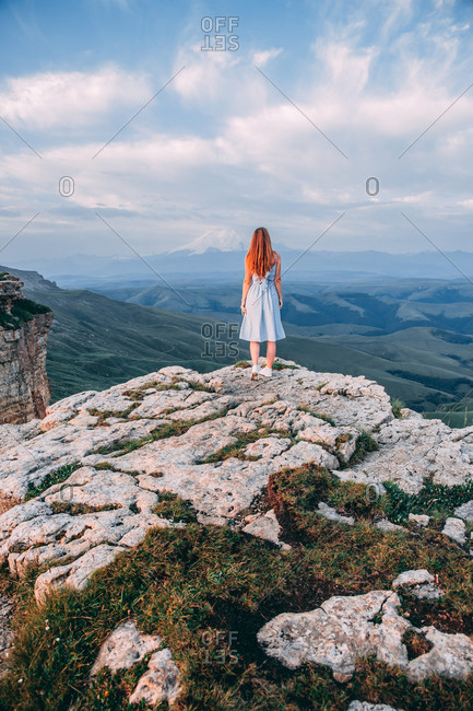Young beautiful girl in a light dress stands raising her arms to the sides on top of the mountain