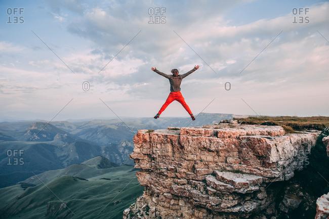 Man jump through the gap between hill