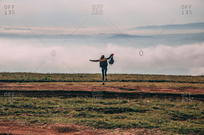 Young sporty girl goes running in the nature Beautiful foggy morning Moody atmosphere