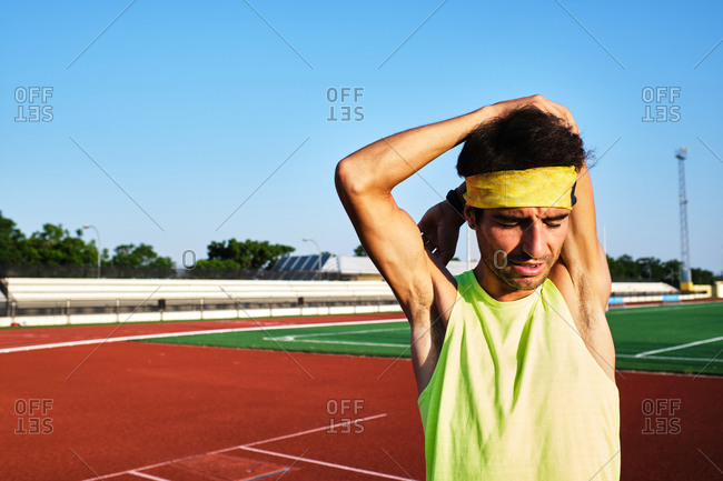Young man practices stretching on the grass after his daily training