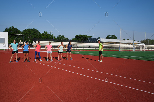 Group of women practice pre-workout stretching with their young trainee