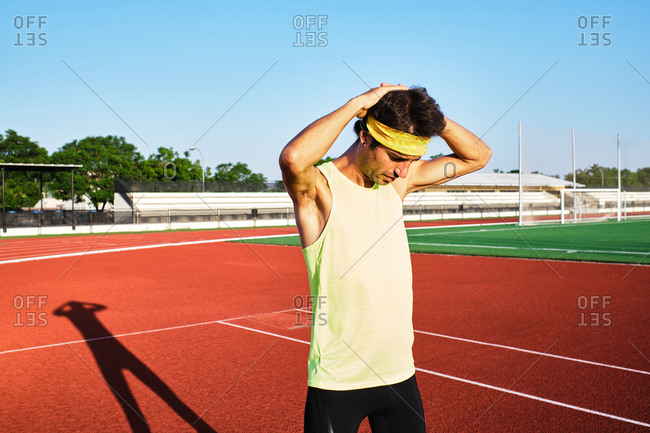 Young man practices his stretches after a hard workout