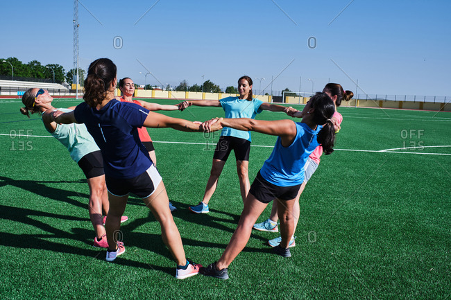 Group of young women practice stretching after their training