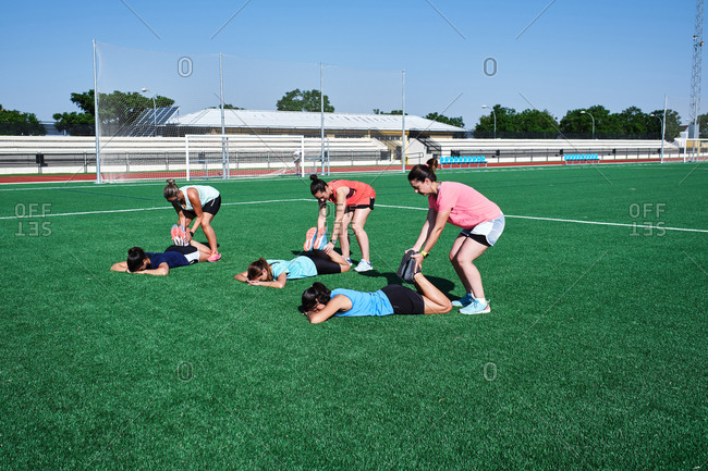 Several young women practice stretching after training