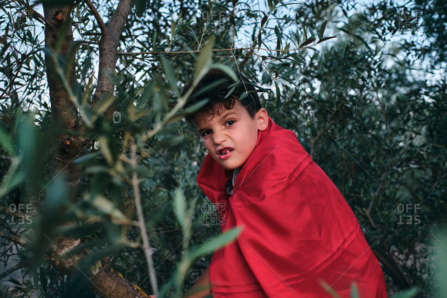 Child disguised as a red superhero rides a tree and makes a mean face
