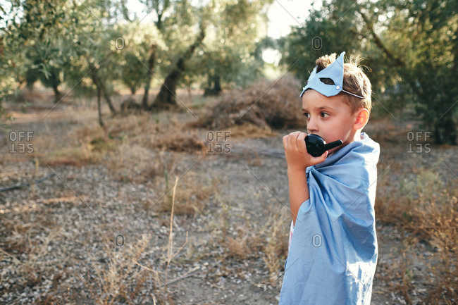 Child disguised as a blue superhero takes the walkie talkie