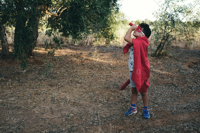 Child disguised as a red superhero takes his red spyglass
