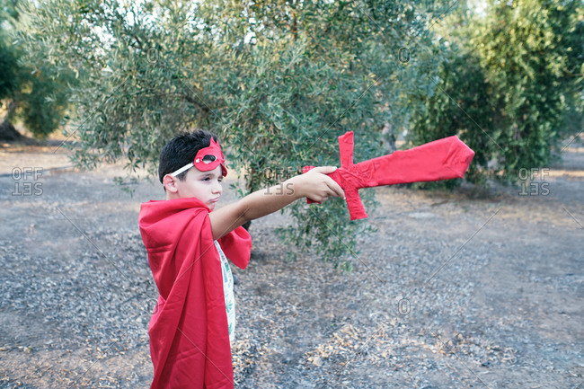 Child disguised as a red superhero points his sword at the ghosts