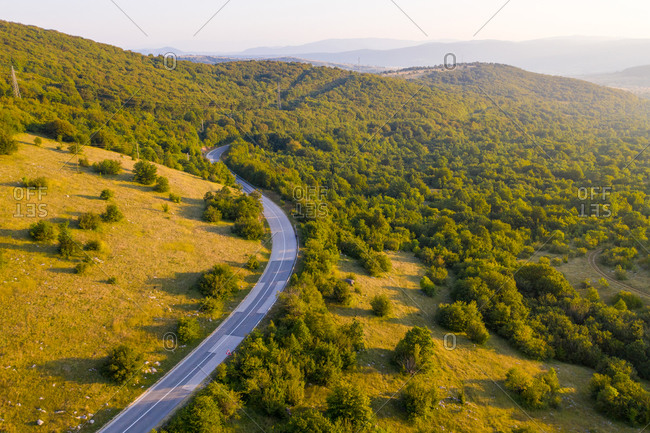 Aerial view of empty road crossing the countryside during sunset