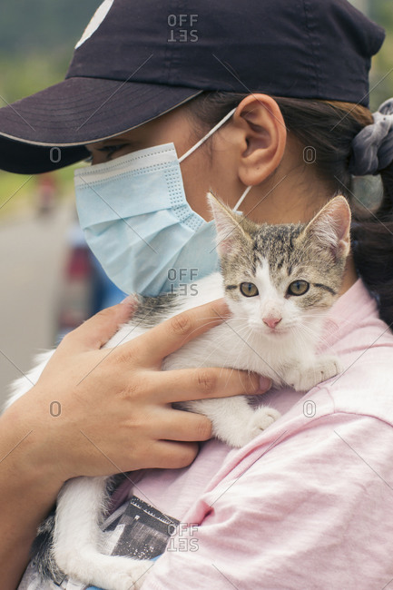Woman wearing face mask and black cap, carrying a young white and gray cat on her shoulders