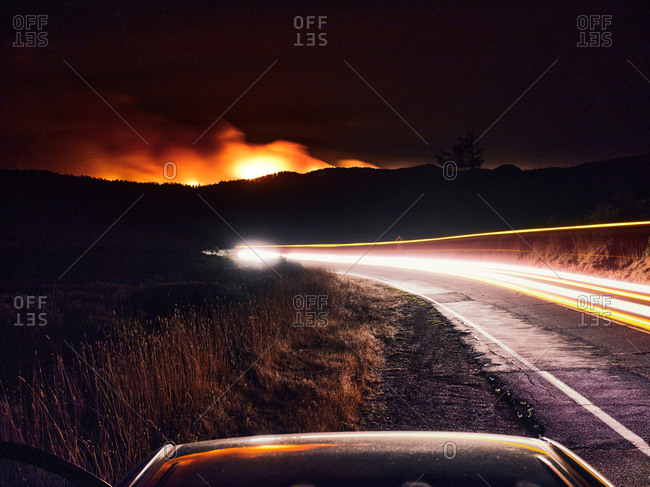 Blurred headlights on a dark road, Woodward Fire burns in Point Reyes.