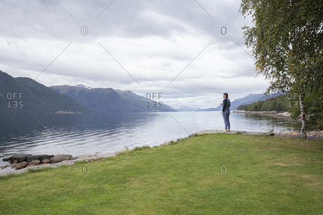 Male drinking coffee outdoors in a fjord in Norway