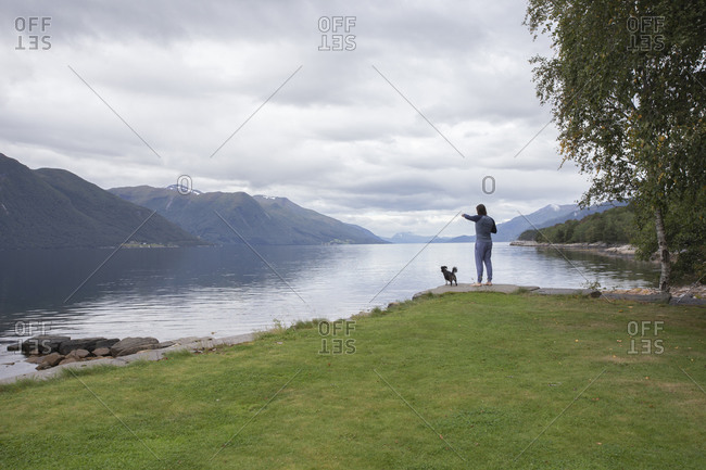 A man and his small dog looking across the fjord in Norway