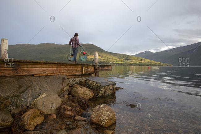 A fisherman walks along a dock in Norway