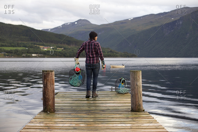 A man holding a crab pot off a dock in Norway