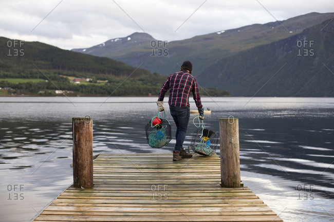 A fisherman about to drop some crab pots off a dock in Norway