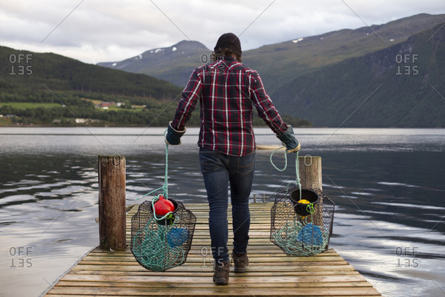 A man carries two crab pots along a dock in a fjord