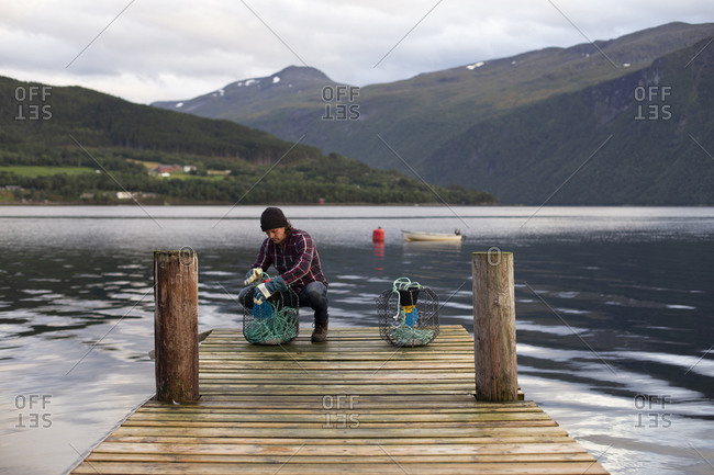 A Norwegian working on some crab pots on a dock by the fjord