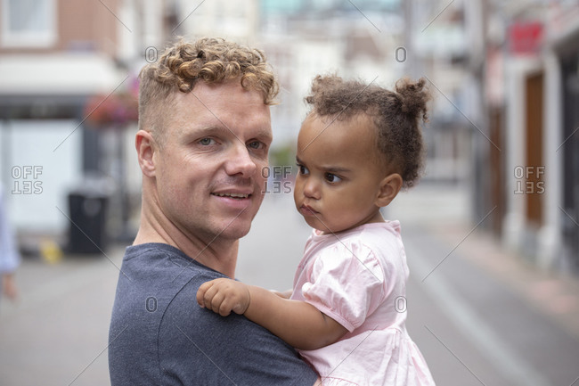 A red head father holding his daughter