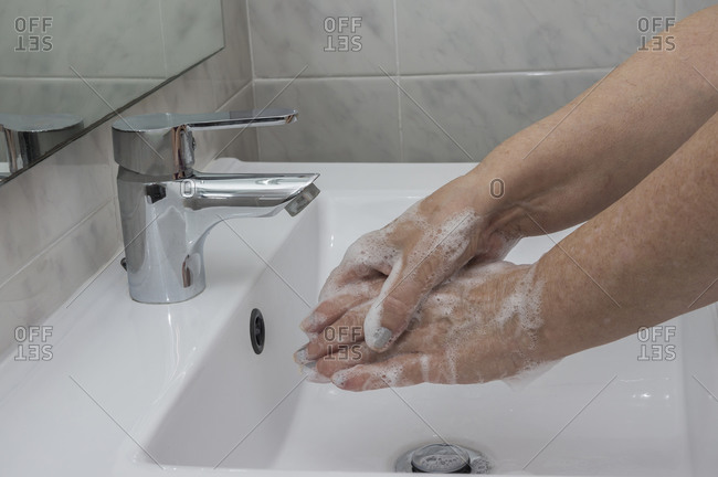 Woman washes her hands by surgical hand washing method.