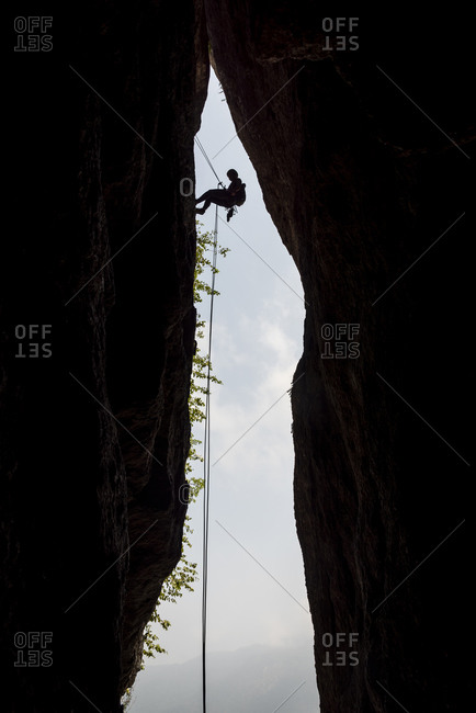 Silhouette of female rock climber rappelling on mountain crack