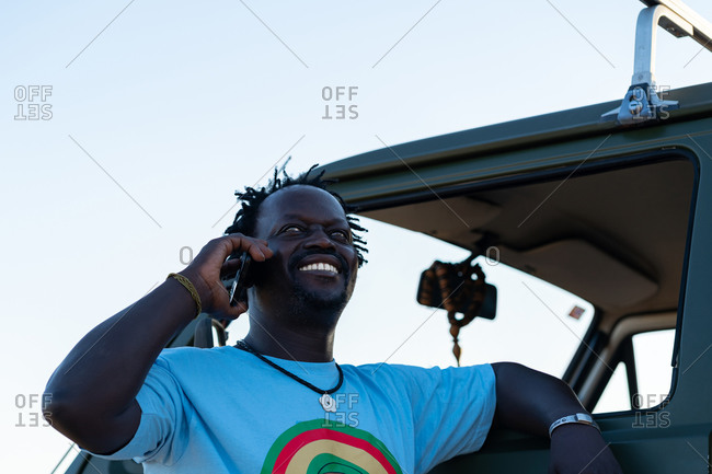 Middle aged black man smiling talking on the phone in his green camping van