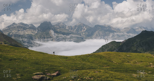 Young woman hiking through Pyrenees with Mount Aspe in the background.