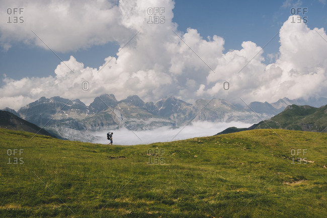 Young man hikes at Mt Aspe in the Pyrenees, while carrying his son.
