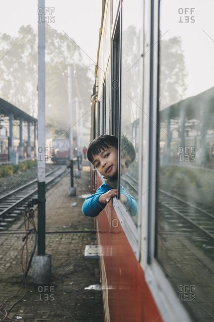 Young boy smiling through Toy Train window at Kalka Station, Haryana, India