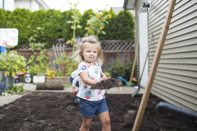 Young girl helping with a landscaping project in her backyard.