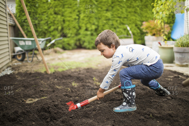 Young boy shoveling dirt, helping dad with landscape project.