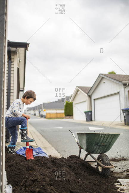 Young boy shoveling dirt into wheelbarrow in back alley