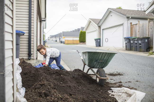 Young boy scooping pile of soil into wheelbarrow in back alley