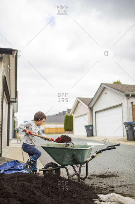 Young boy lifting shovel full of soil into wheelbarrow in back alley