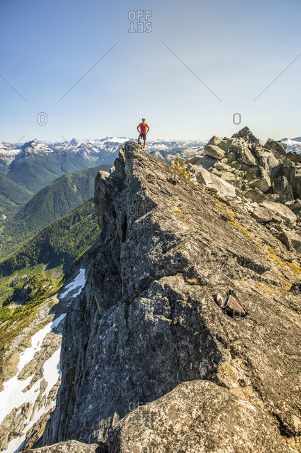 Trail runner stands on mountain summit, edge of a cliff.