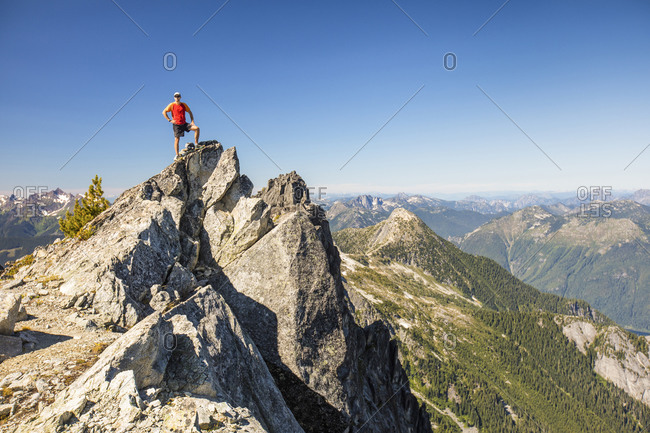 Backpacker stands on summit of mountain after a long day of hiking