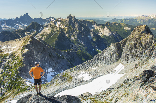 Trail runner looks out at view from the summit of a mountain.