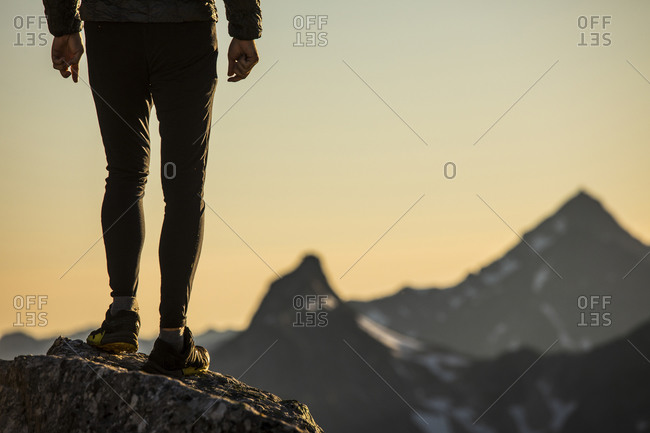 Lower half of trail runner standing on mountain summit with view