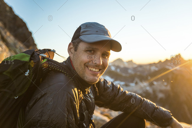 Portrait of backpacker smiling, enjoying night in the mountains.